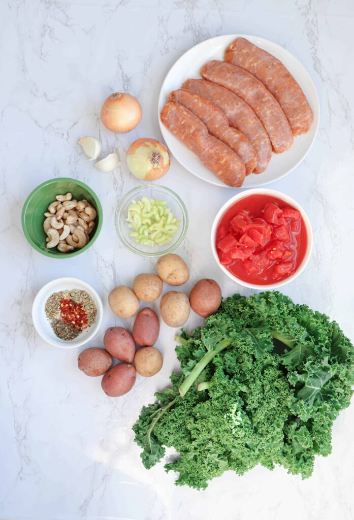 Sausage, kale, tomatoes in a bowl, onions, oil and spices lying on a marble countertop