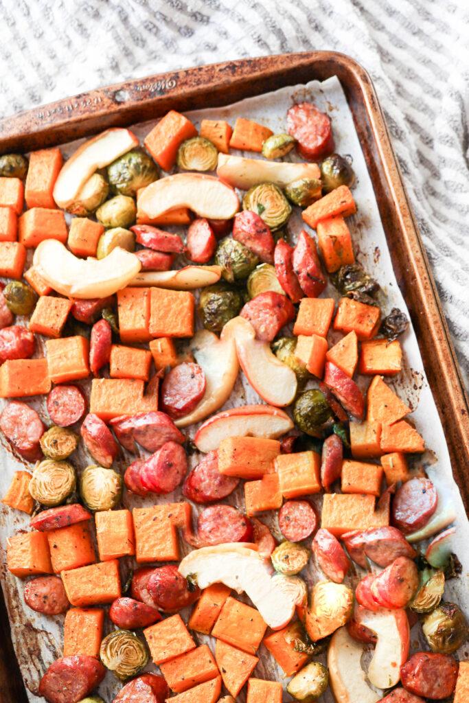 close up of sausage, apple and veggies on a sheet pan