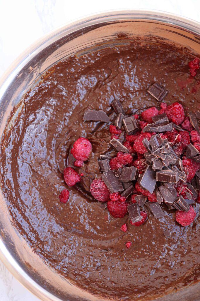 brownie batter with chocolate chunks and raspberries