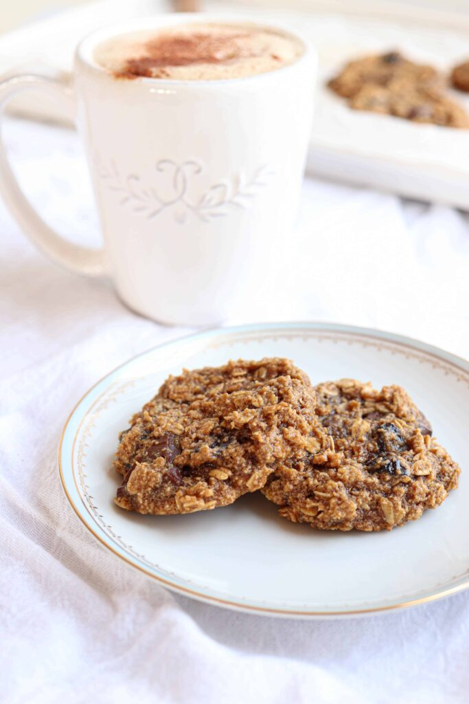 two cookies on a plate with a mug of coffee