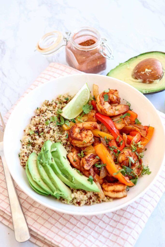 a white bowl with shrimp, peppers, onions, sliced avocado and quinoa