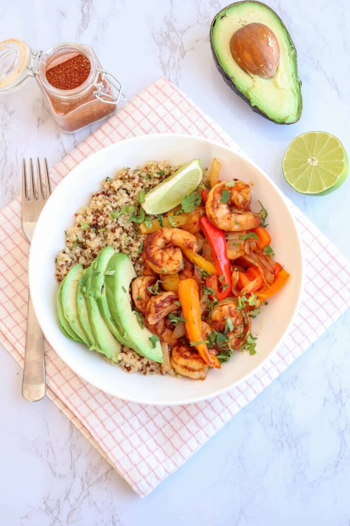 a bowl of shrimp, peppers, onions over quinoa with cilantro and sliced avocado and lime