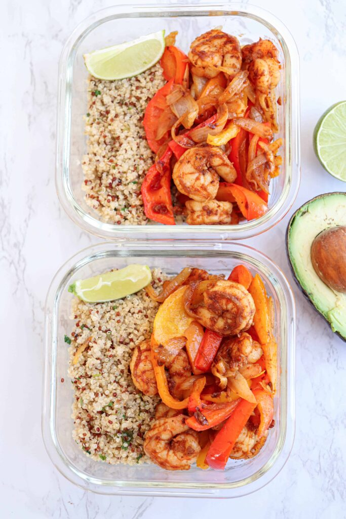 2 glass containers with shrimp fajita bowl meal prep with quinoa and lime