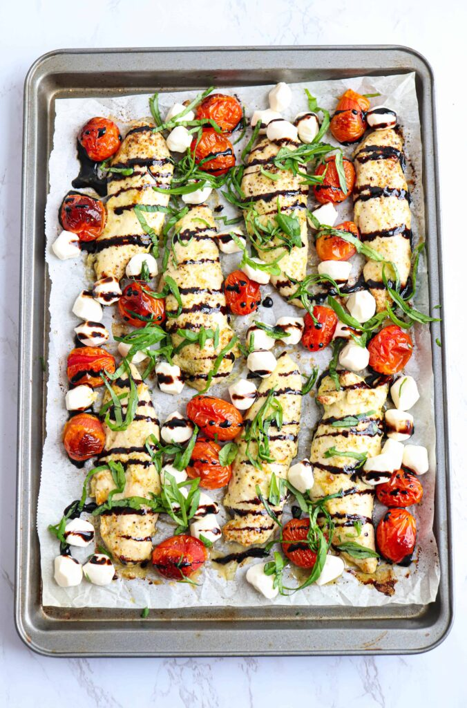 chicken tenders on a sheet pan with tomatoes, mozzarella balls, basil and balsamic reduction