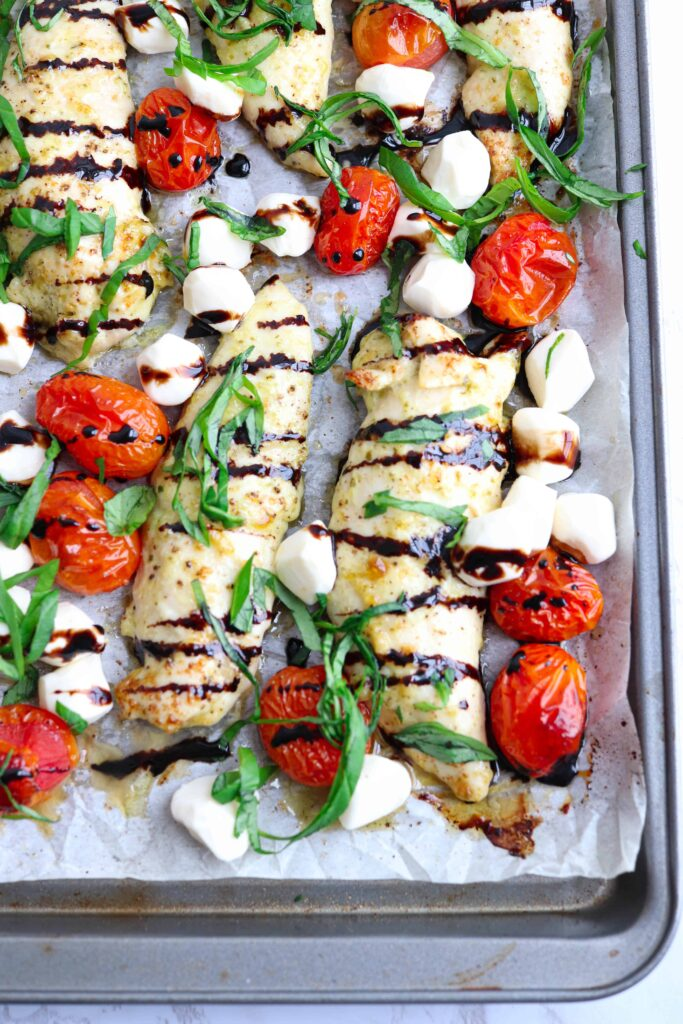 close up of a sheet pan with chicken tenders, roasted cherry tomatoes, basil. balsamic