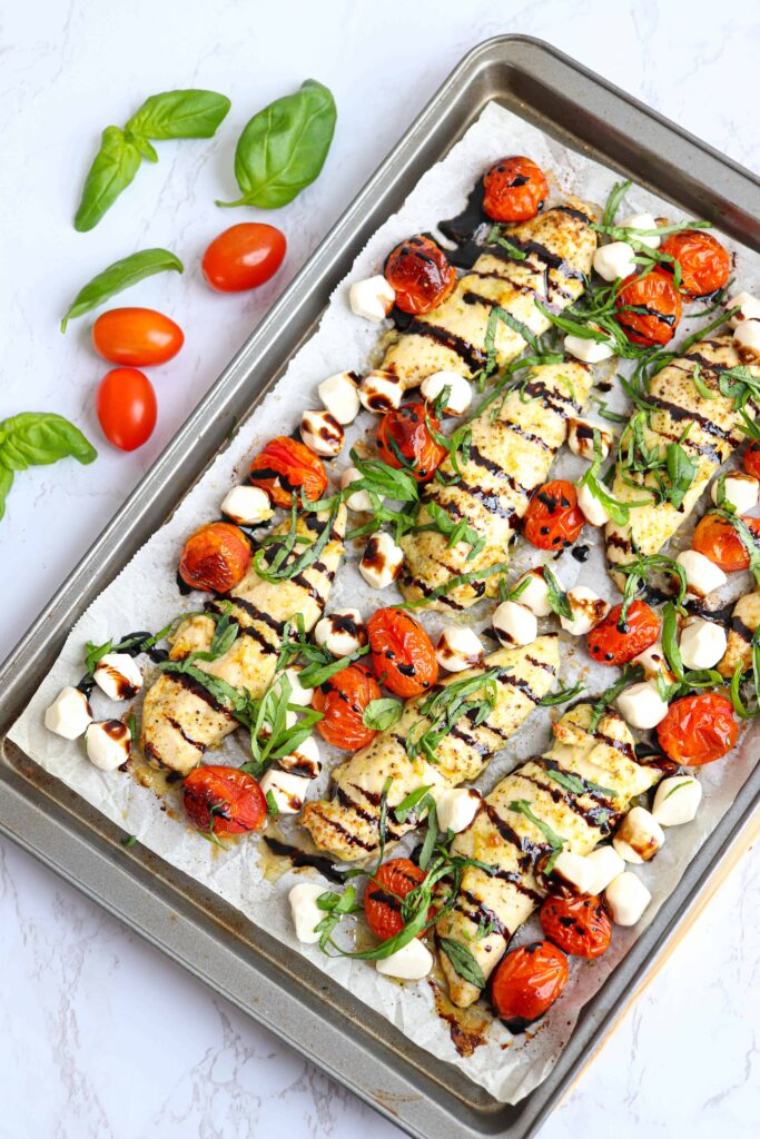 sheet pan with chicken caprese dish baked at an angle on the counter