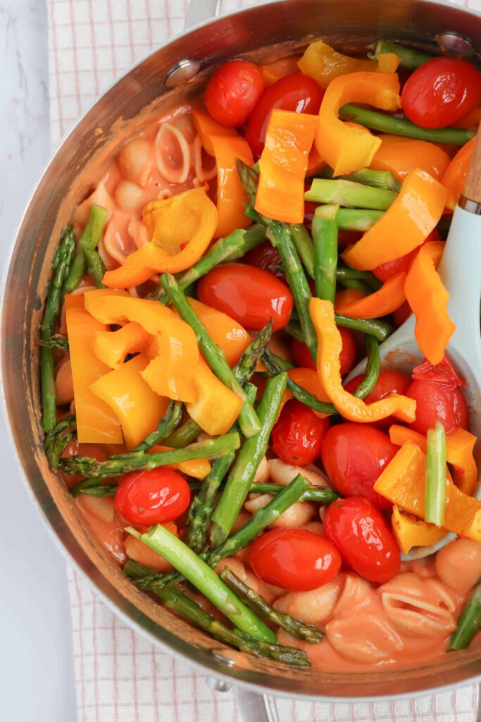 a pot of pasta with sauce, peppers, cherry tomatoes and asparagus