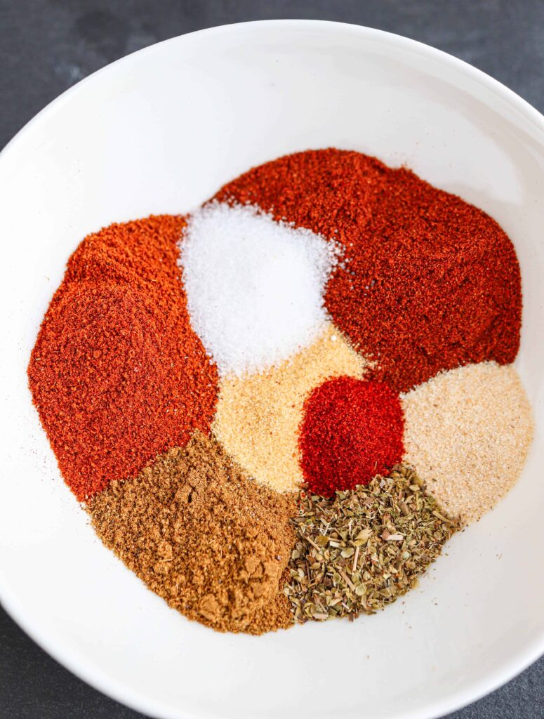 a closeup of taco seasoning 8 spices in a white bowl, unmixed