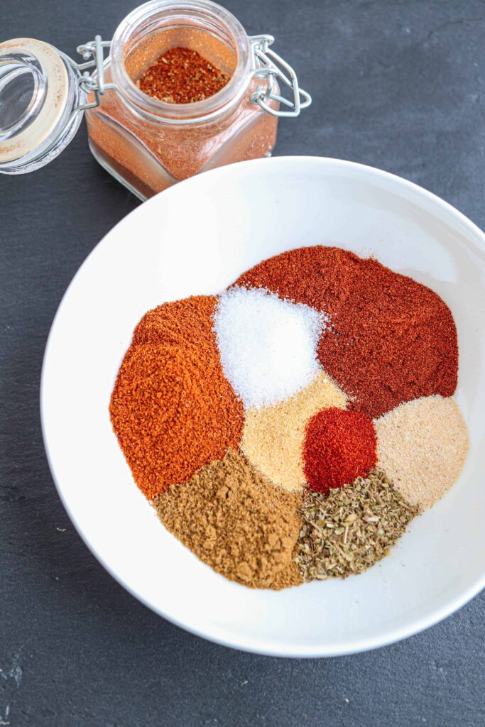 a close up of taco seasoning spices in a white bowl on black background with a small spice jar on top