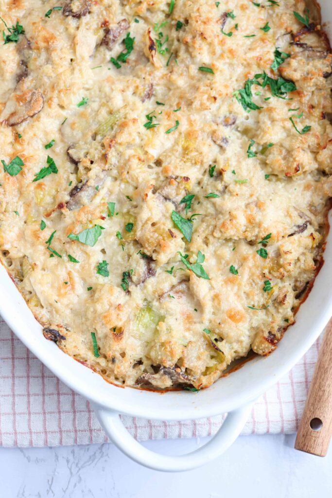 chicken and mushroom cauliflower rice casserole in a white casserole dish on white background close up