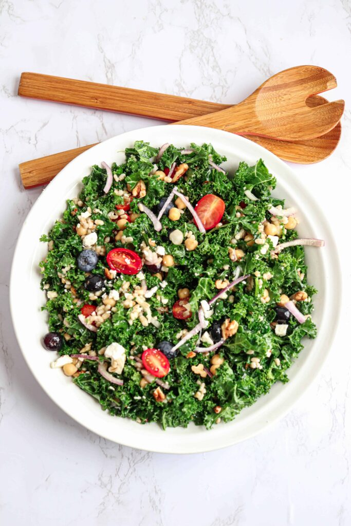 salad bowl with kale, barley, tomatoes and blueberries with 2 wooden spoons