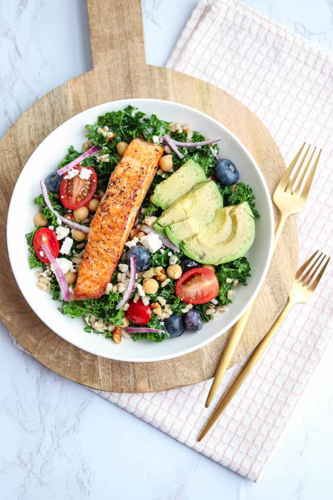 seared salmon kale and barley salad bowl on a wooden board with forks