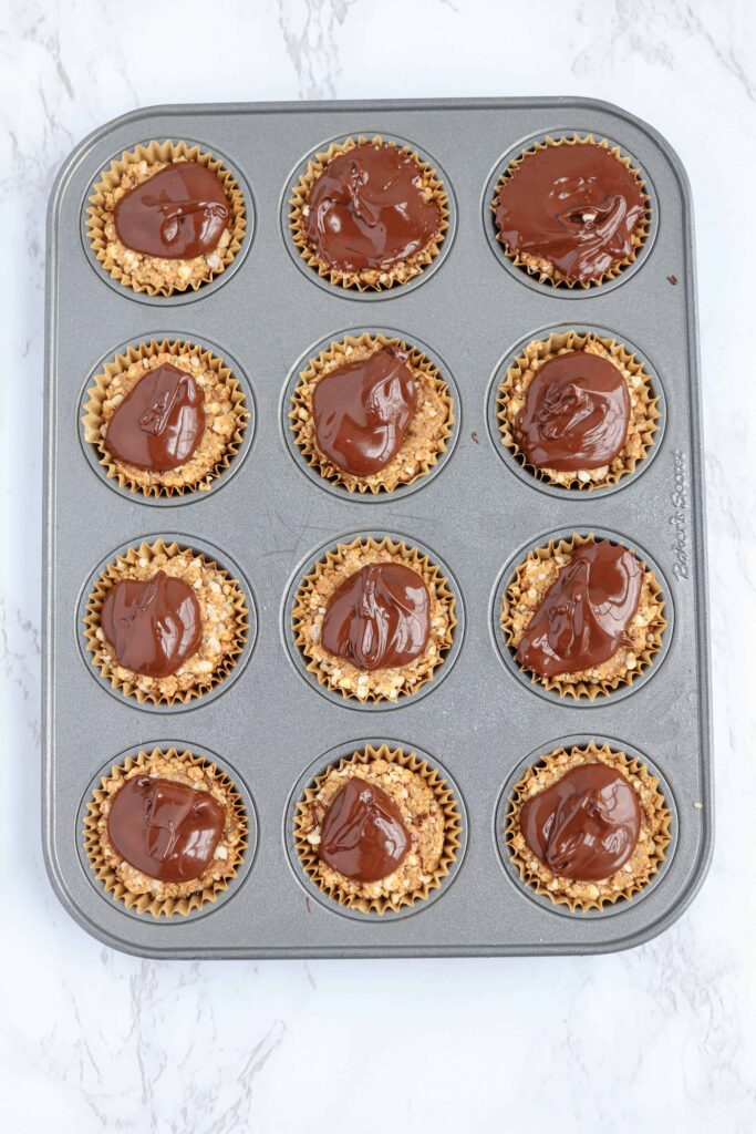 almond butter rice cups in a muffin tin with chocolate melted on top