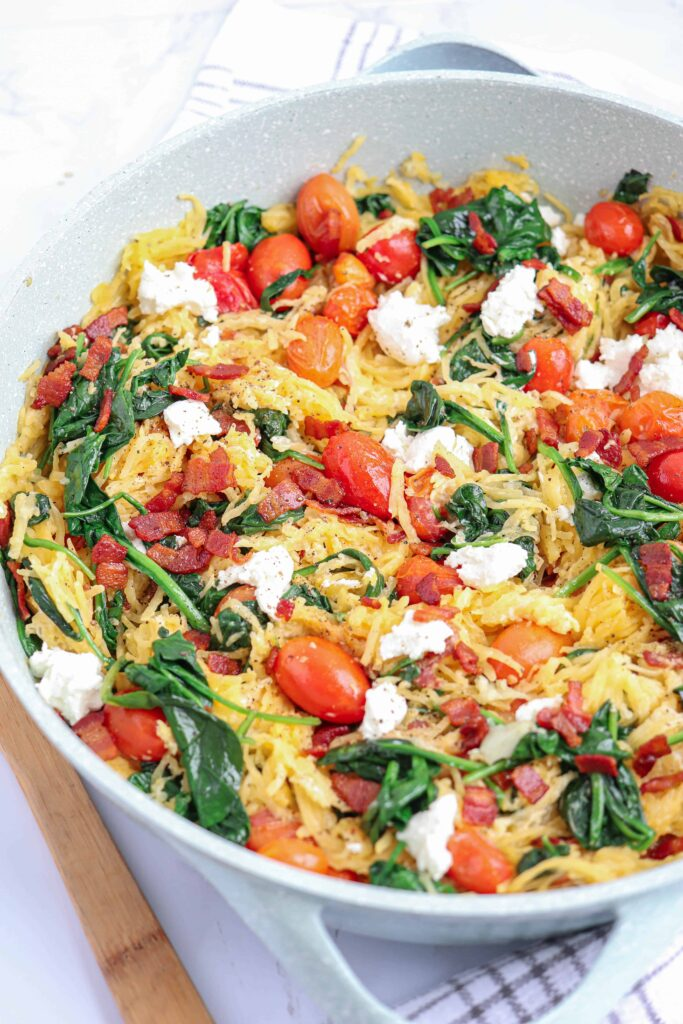 spaghetto squash with bacon, spinach, tomatoes and goat cheese in a light blue skillet