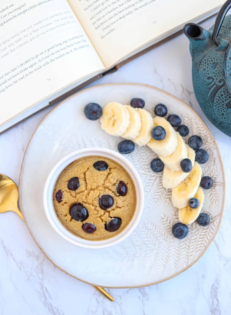 ramekin with banana baked oats with blueberries on a plate with a side of fruit