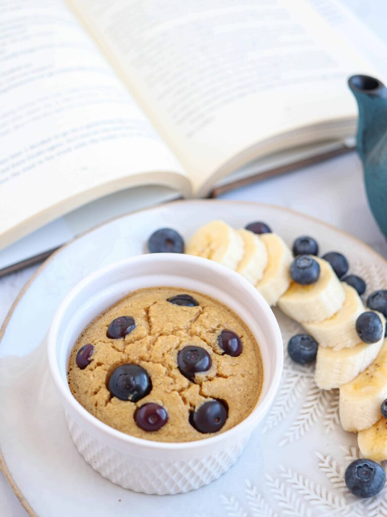 a ramekin with banana baked oats with blueberries on top on a plate with a side of fruit and a book in the background