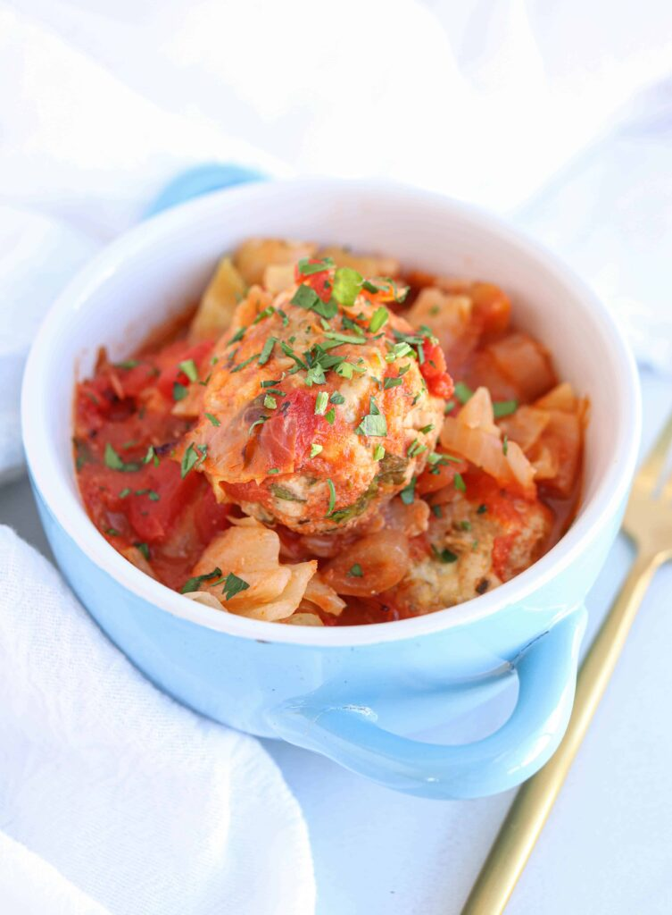 unstuffed cabbage rolls in a blue and white bowl on white background