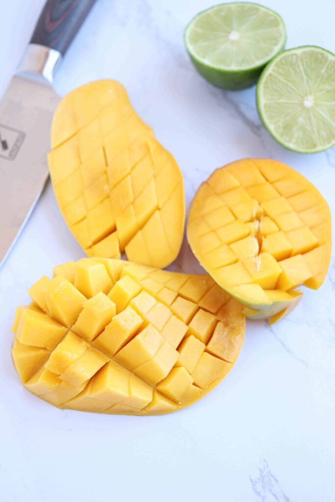 mango with cut grid pattern and limes on the side on white marble