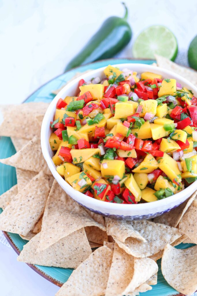 a white bowl of fresh mango salsa with red peppers and cilantro surrounded by tortilla chips