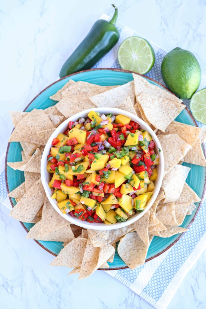 fresh mango salsa in a white bowl on a blue plate with tortilla chips around on white marble with jalapeno and lime in the background