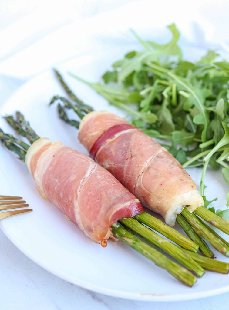 two prosciutto wrapped asparagus stuffed chicken rollups on a white plate with a side of arugula
