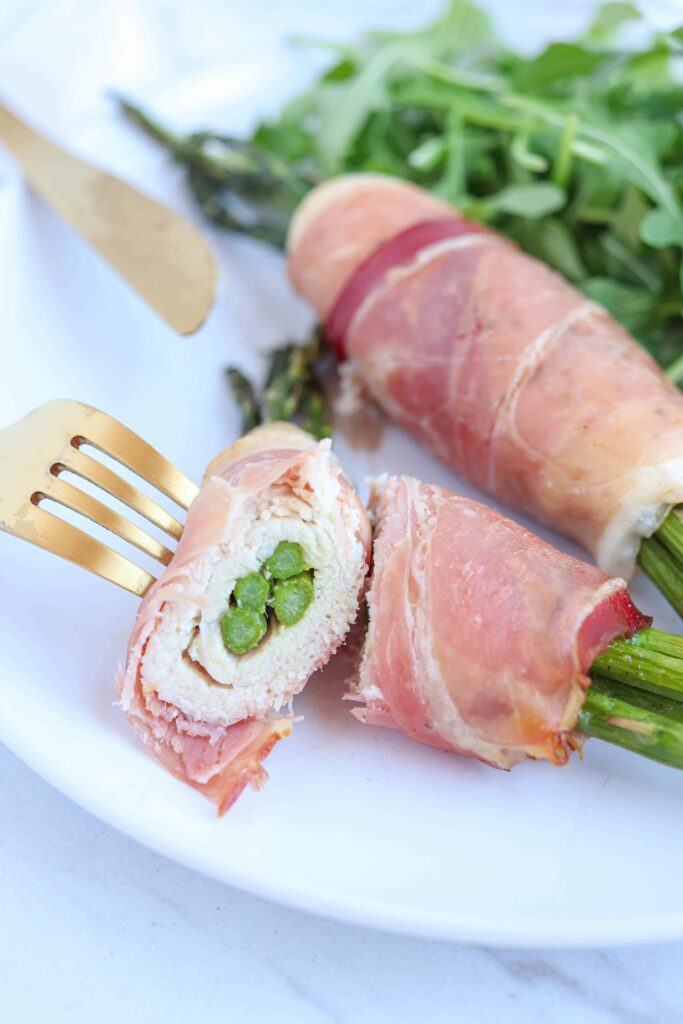 two prosciutto wrapped asparagus stuffed chicken roll ups with one of the roll ups cut in half on a fork and a side of arugula