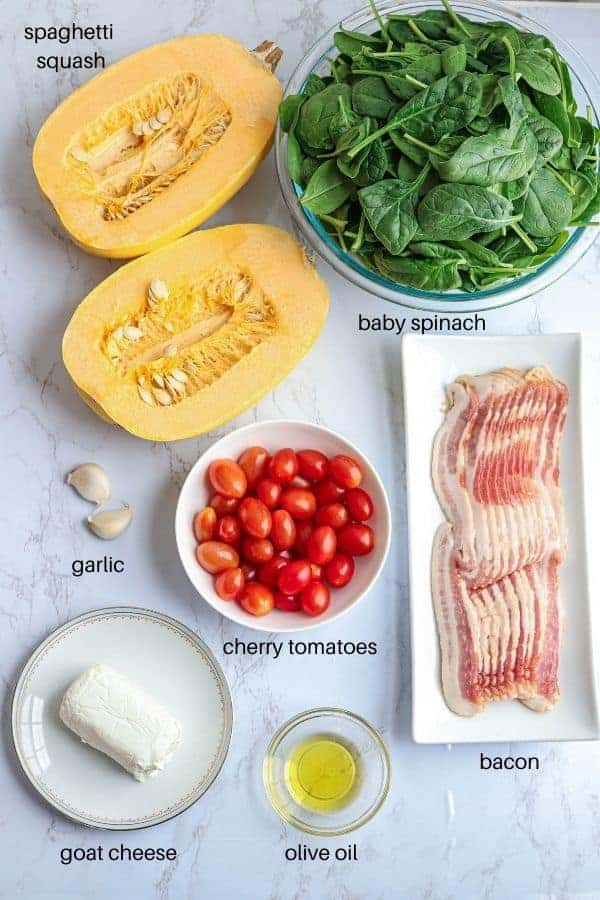 spaghetti squash with bacon, spinach, tomatoes & goat cheese ingredients on white marble