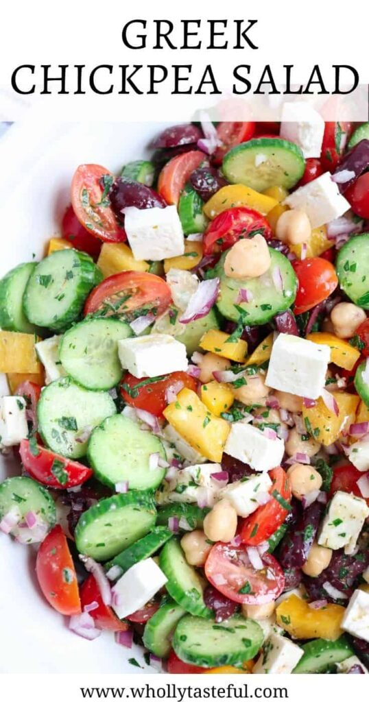 """a closeup of Greek chickpea salad with tomatoes, cucumbers, red onions, olives, feta cheese and a caption on top with the title """"Greek Chickpea Salad"""""""