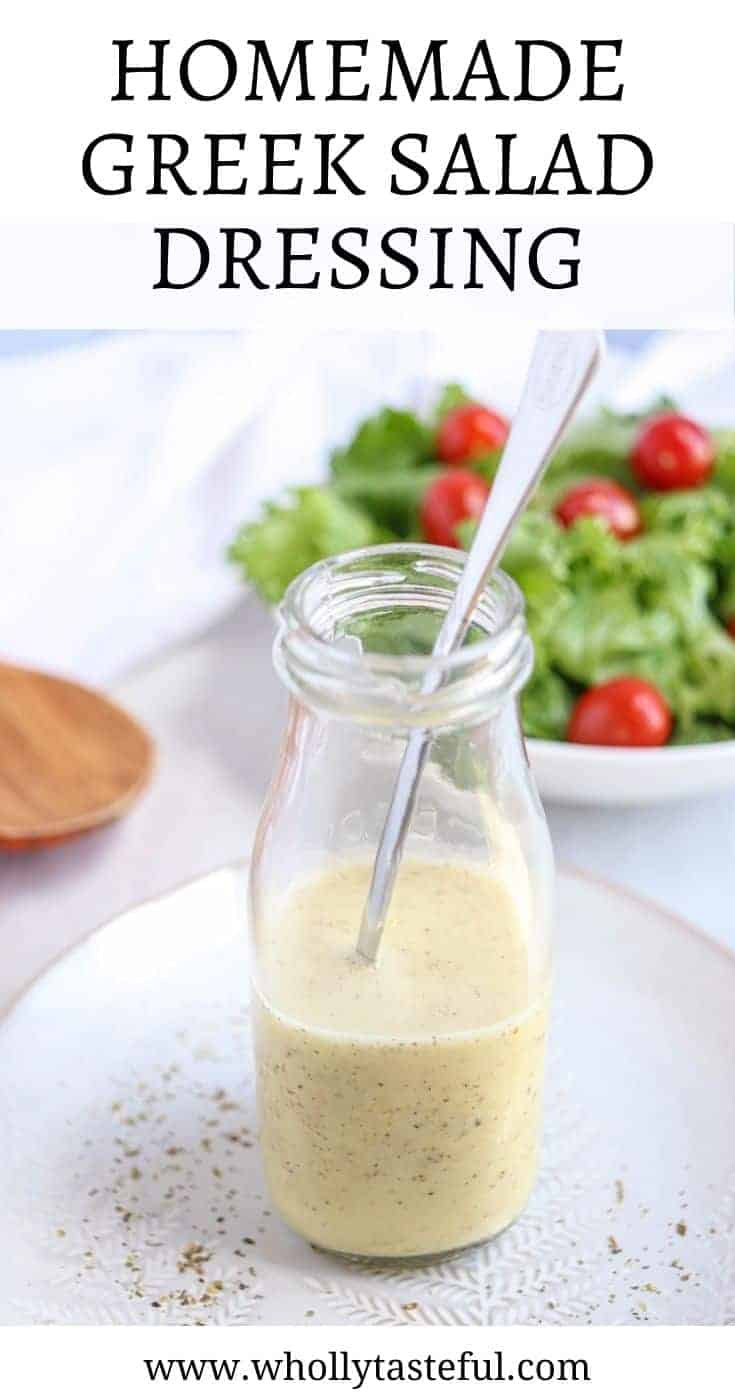 """glass bottle with Greek salad dressing and a long spoon on a plate with a green salad in the background and a pin title on top saying """"Homemade Greek Salad Dressing"""""""