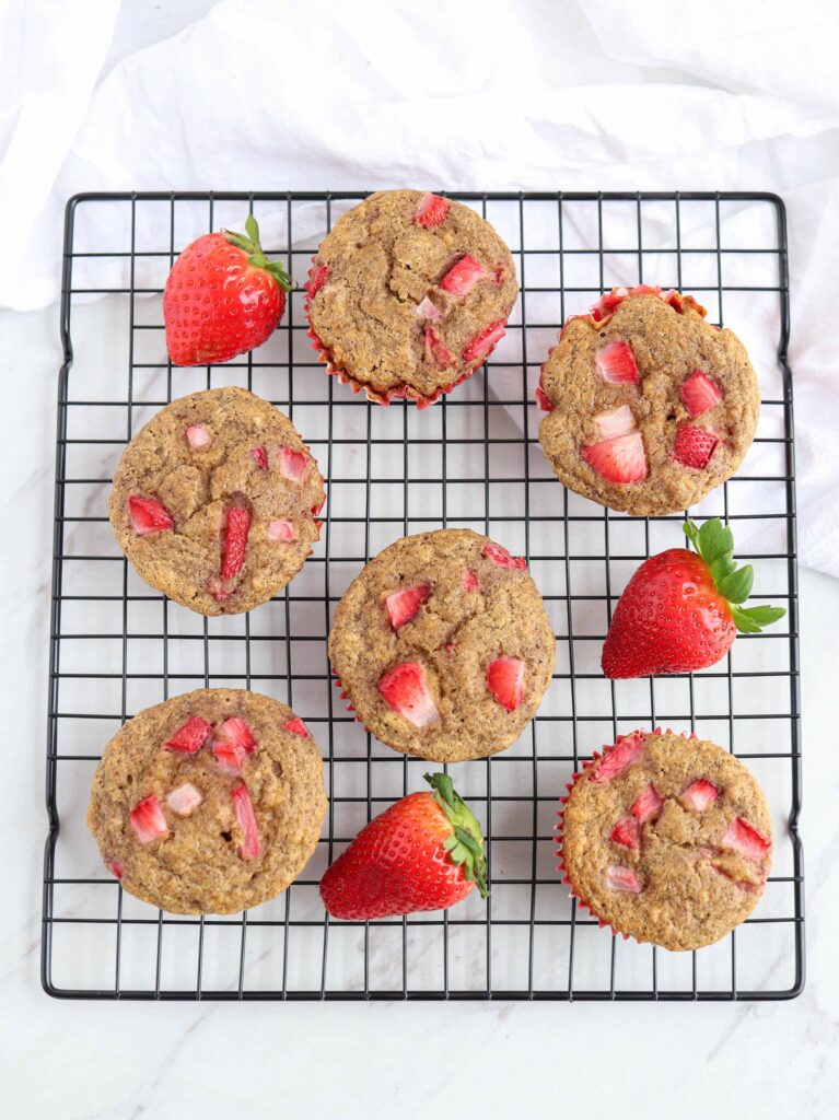 a black cooling rack with strawberry banana muffins in red muffin liners and 3 strawberries around