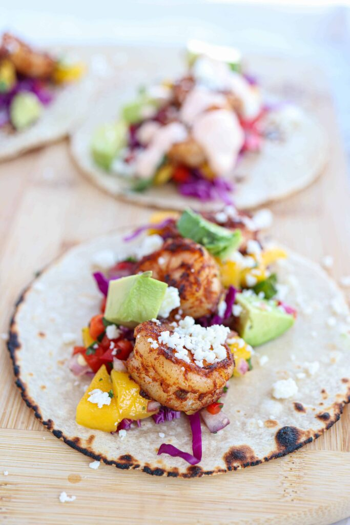 corn tortilla with charred edges, topped with shrimp, avocado and mango salsa on a wooden board