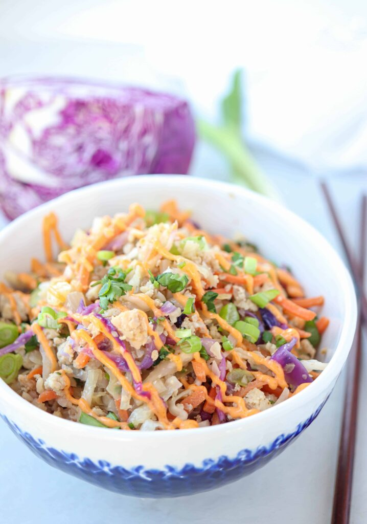 meat and vegetables with sriracha mayo drizzle in a white and blue bowl with red cabbage and scallions in the background and chopsticks on the right