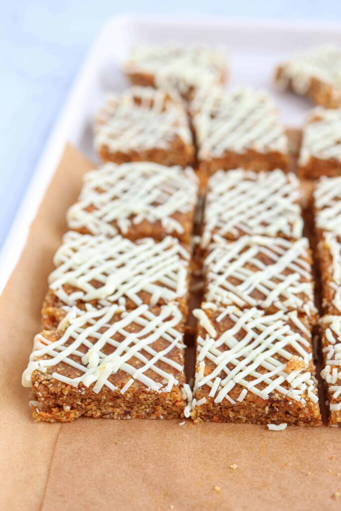 no bake carrot cake bar squares with white chocolate drizzle on brown paper