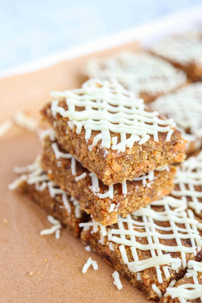no bake carrot cake bars with white chocolate drizzle on brown paper stacked to show structure