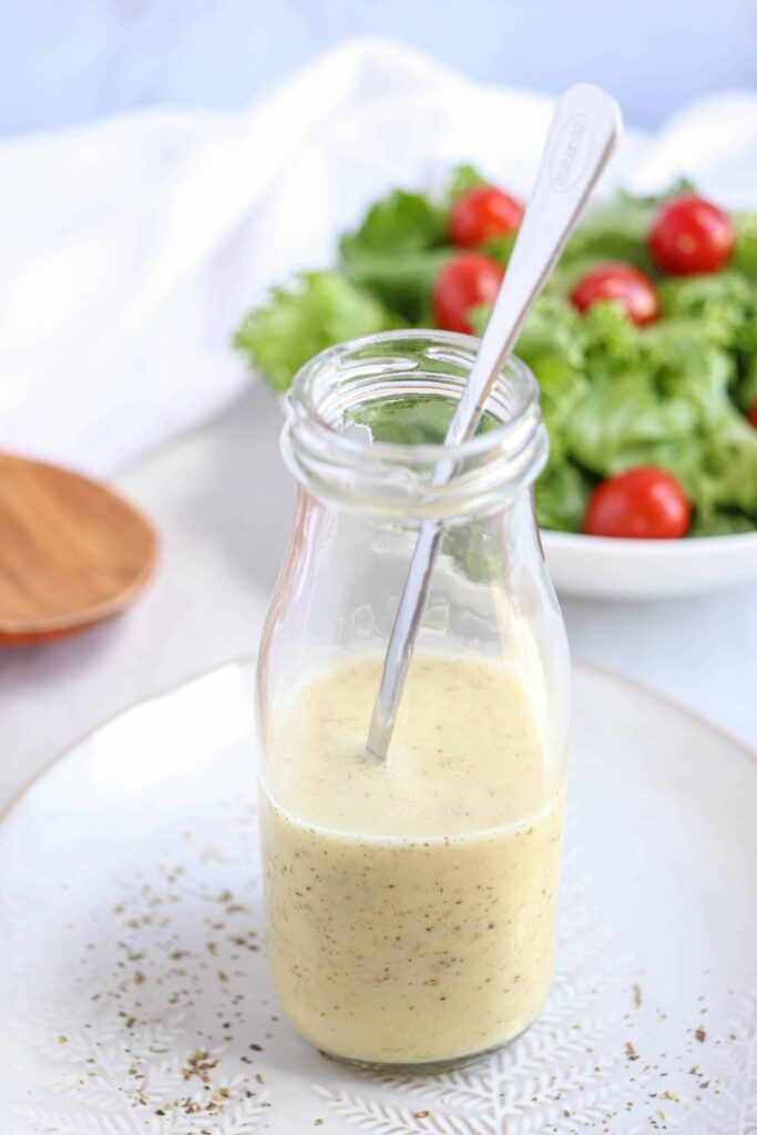 Greek salad dressing in a glass bottle on a plate with a salad in the background