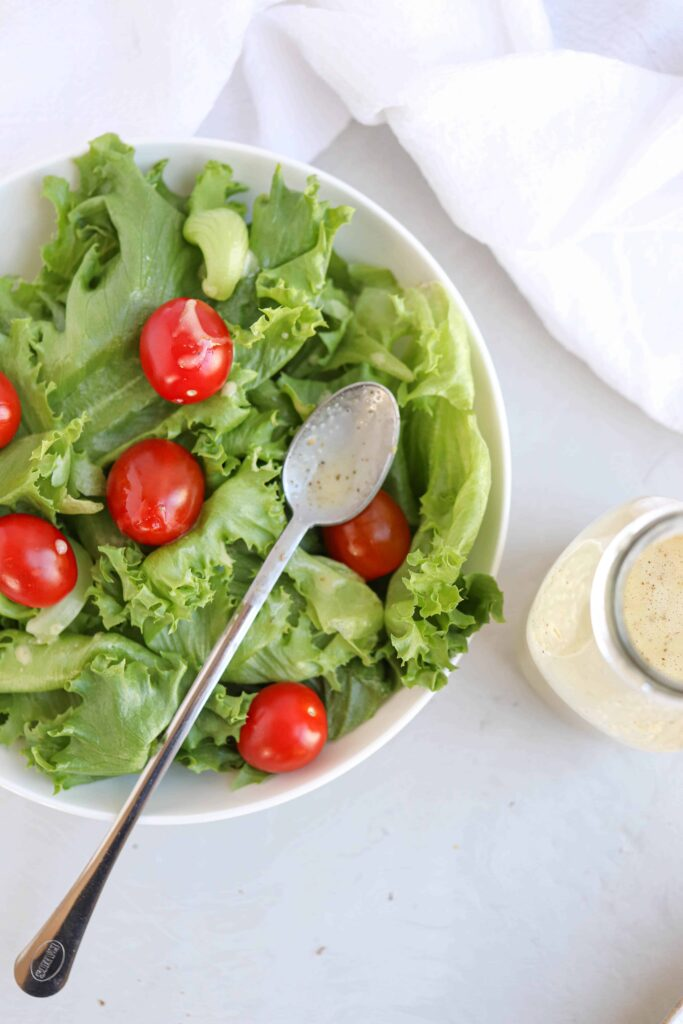 a green salad with cherry tomatoes in a white bowl with a long steel spoon on light gray surface with a white kitchen towel and a glass bottle with Greek salad dressing