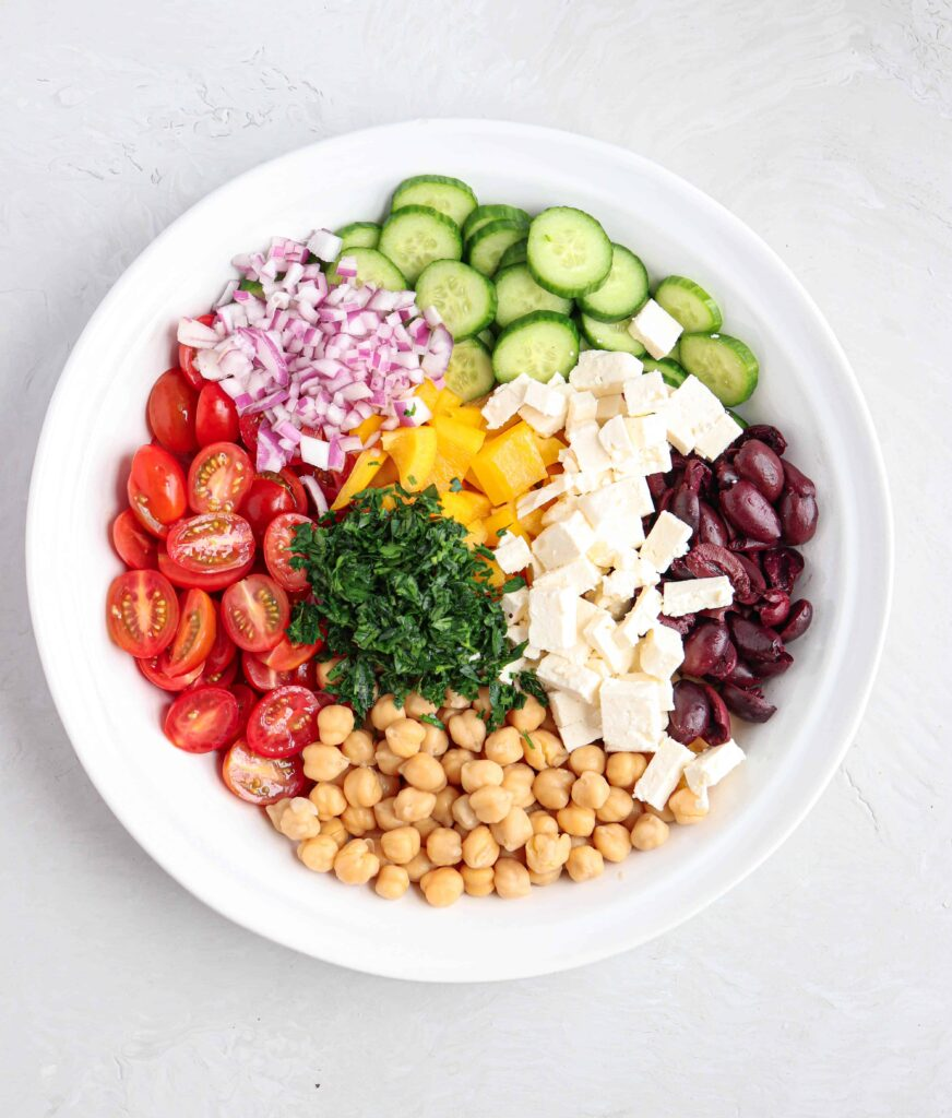 A large white bowl with Greek chickpea salad before mixing the ingredients: tomatoes, cucumbers, feta cheese, olives, parsley, yellow bell peppers and red onions on light gray background