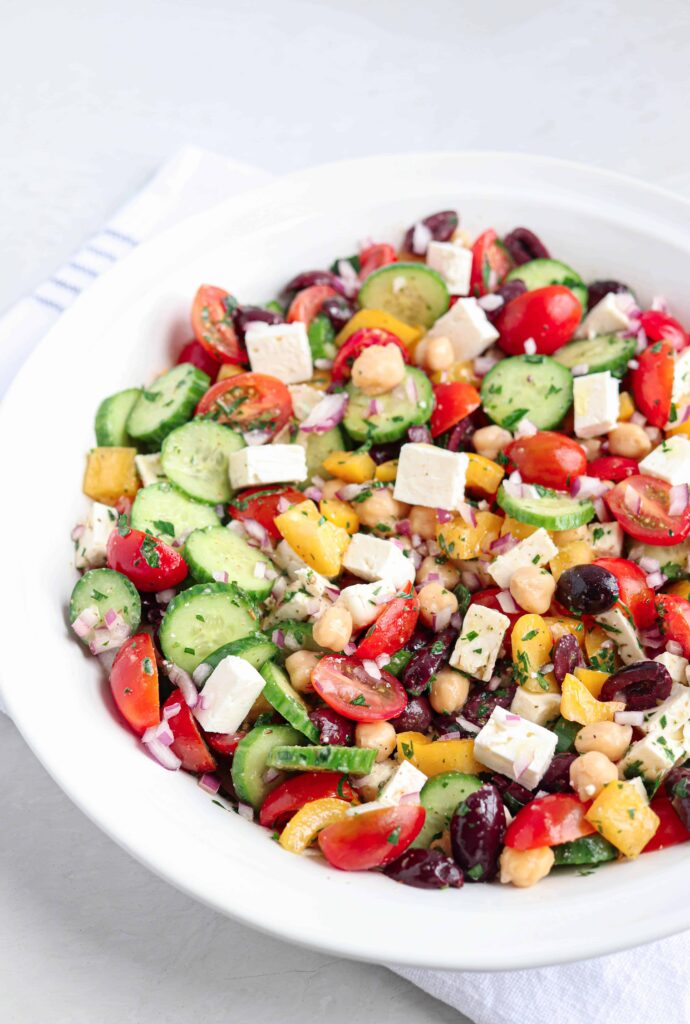 a white bowl with Greek chickpea salad with tomatoes, cucumbers, olives, feta cheese, chickpeas and red onion on a white kitchen towel on a light background