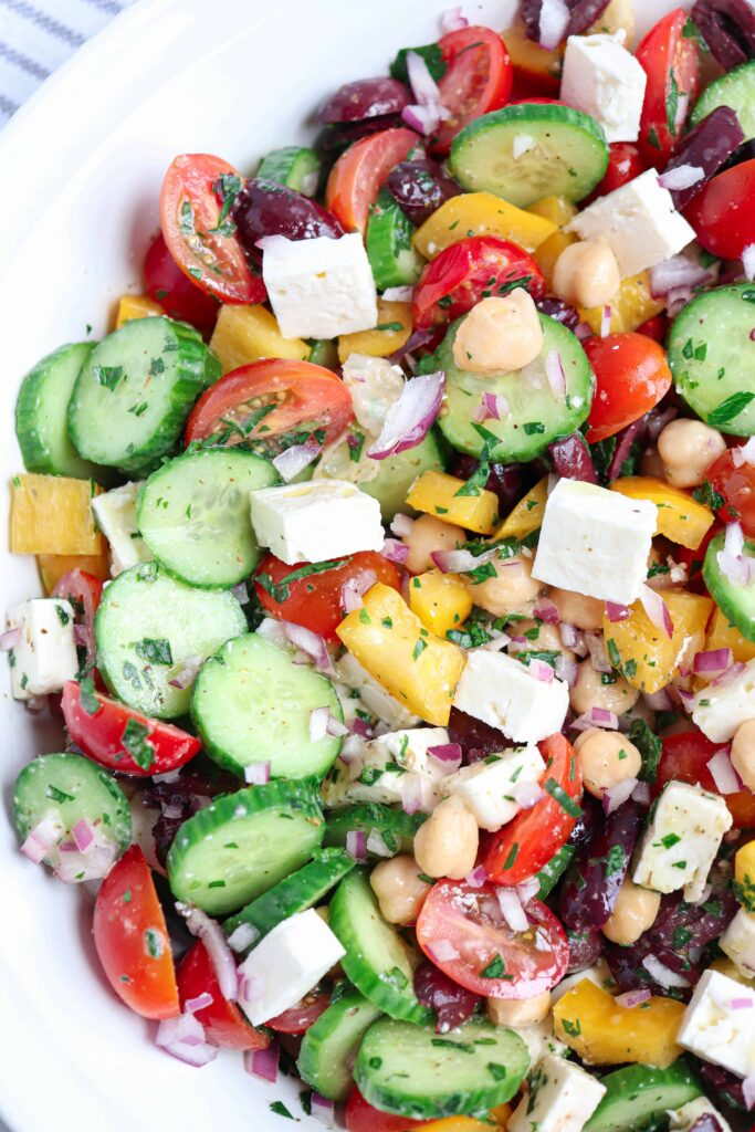a closeup of chopped tomatoes, cucumbers, red onions, yellow peppers, red onions, feta cheese, kalamata olives and parsley, dressed