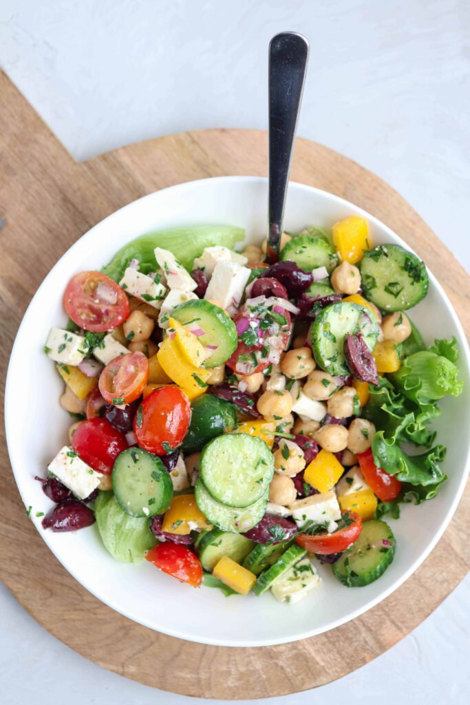 a white bowl with Greek chickpea salad on a bed of lettuce on a wooden round board and a fork sticking out of the bowl