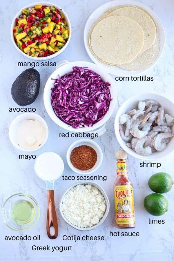 shrimp tacos ingredients laid out on white marble surface