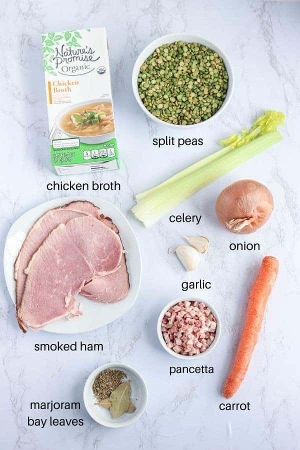 split peas, chicken broth, smoked, pancetta, carrot, ham, garlic, celery, onion and herbs on white marble countertop