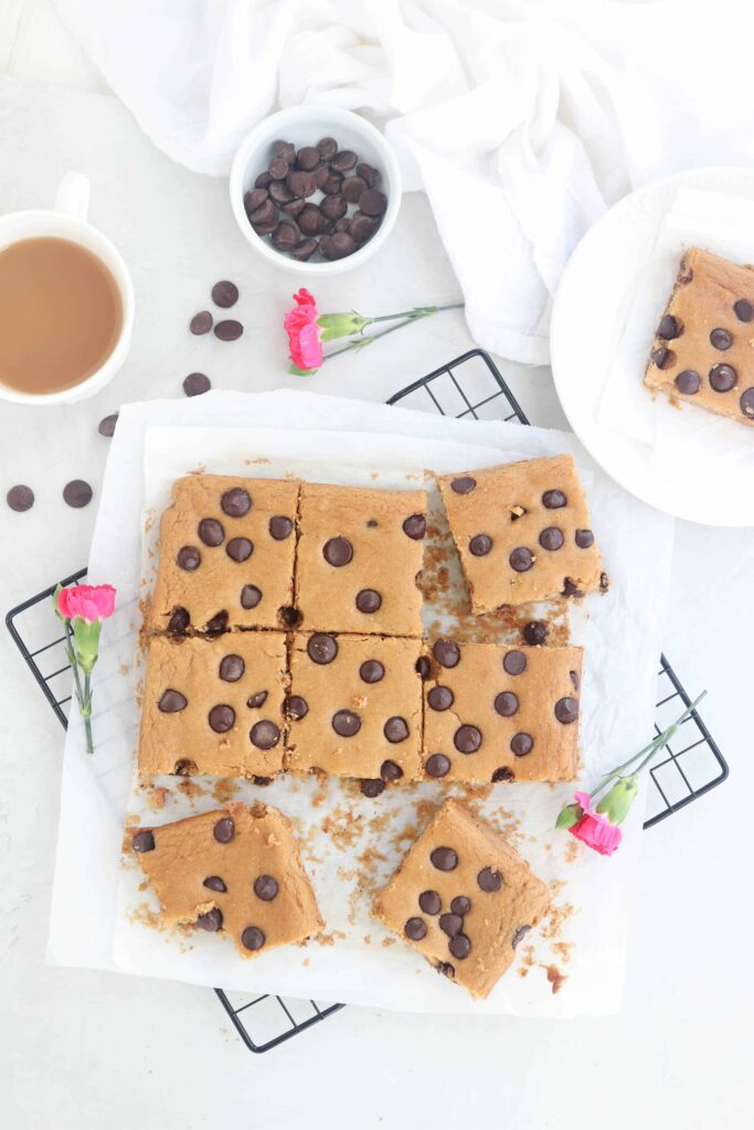 chickpea blondies with chocolate chips cut into squares on white parchment paper on a black cooling rack on light gray surface with 3 pink carnations, chocolate chips and a white cup of tea around