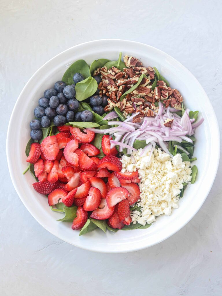 a big white bowl with baby spinach, strawberries, blueberries, red onions, pecans, feta cheese on light gray surface