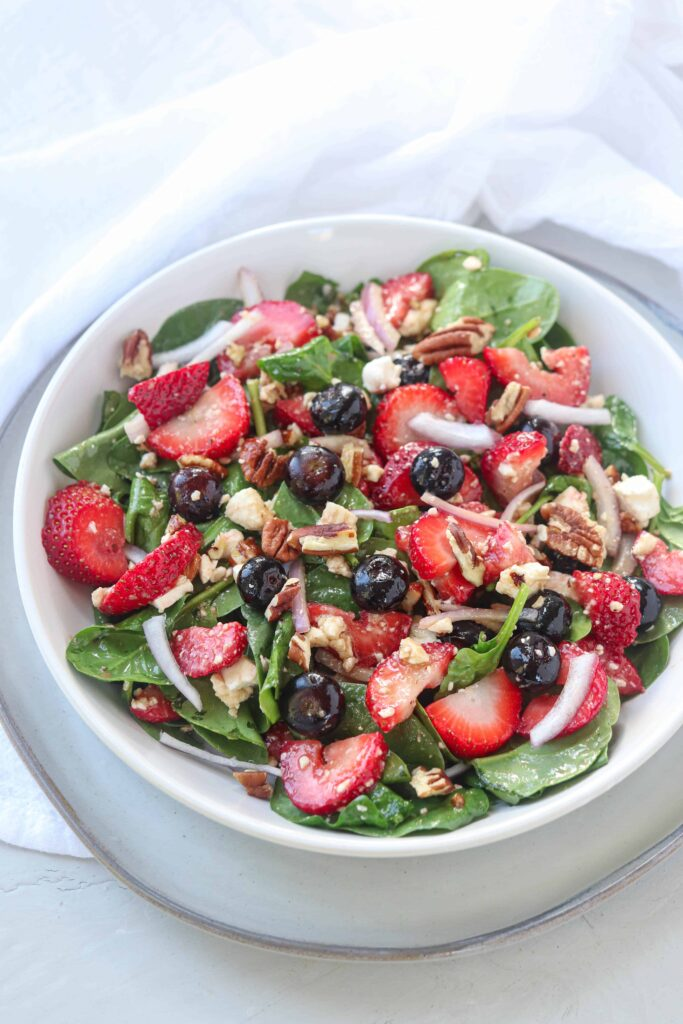 spinach, strawberry salad with blueberries, red onions, feta cheese and pecans on a white bowl on white surface