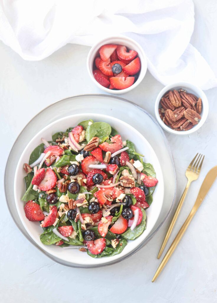 spinach strawberry salad with blueberries, red onions, pecans and feta cheese dressed in a white bowl on a gray plate on light gray surface with golden fork and knife on the right side, a small bowl with berries and a small bowl with pecans