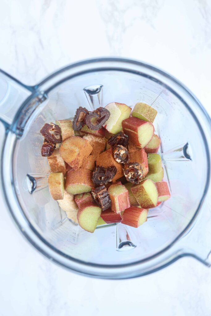 an overhead view of a bowl of a Vitamix blender with rhubarb, dates, cinnamon on white marble surface