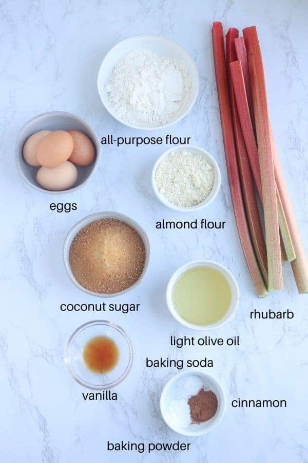 ingredients of rhubarb cake laid out on marble counter with text labels