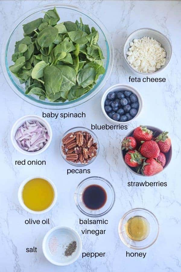 spinach strawberry salad ingredients laid out in bowls on white marble surface with text labels
