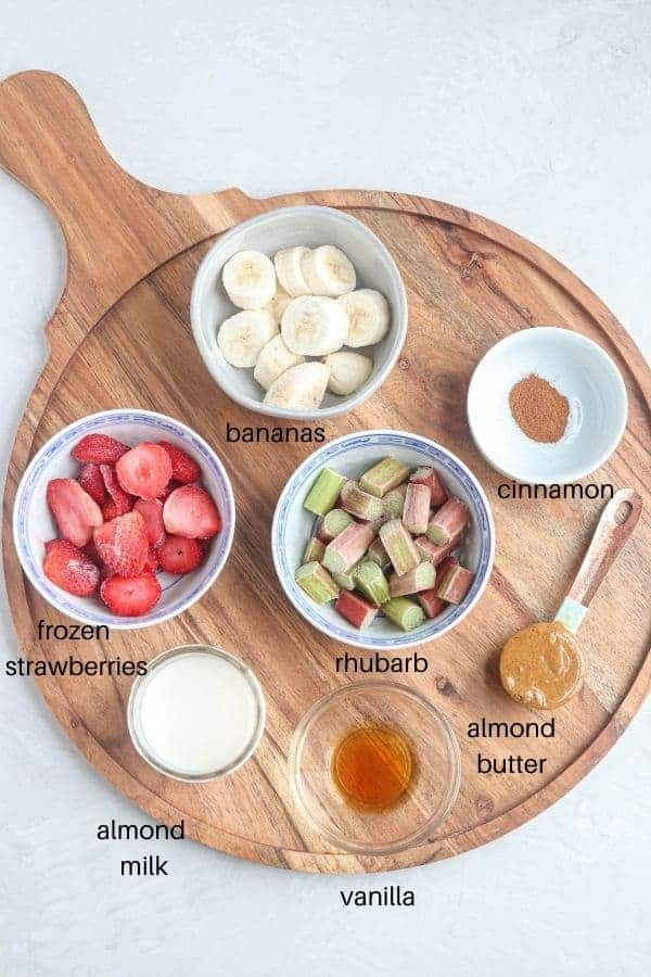 a round wooden board with small round white dishes containing frozen strawberries, rhubarb, bananas, cinnamon, almond milk, vanilla and almond butter on light gray surface
